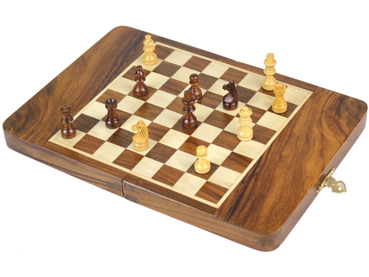 Fully open chess board with pieces on top