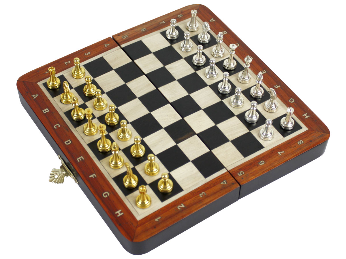 Side view of flat chess board with metal pieces