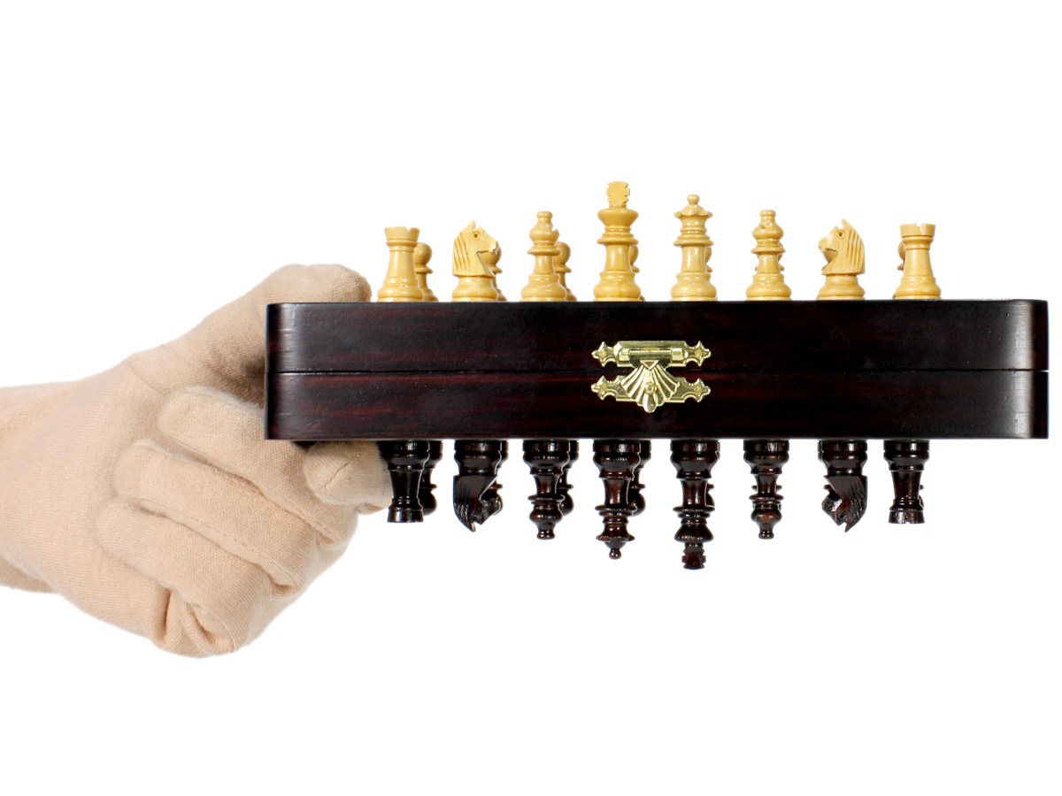 Folding chess board held upside down and magnetic pieces attached to it